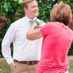 pinning a boutonniere on a groom